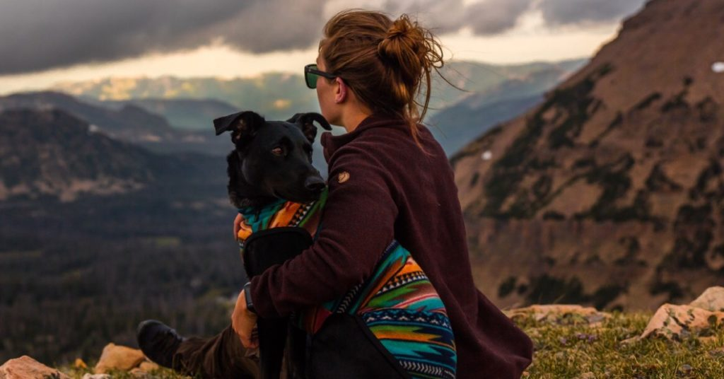 Woman and dog on a mountain (Photo by Patrick Hendry on Unsplash)